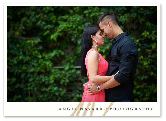 Photo of couple posed in front of grass wall.