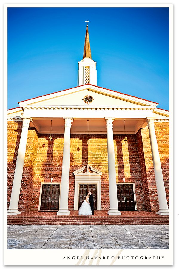Outdoor photo of church with bride and groom.