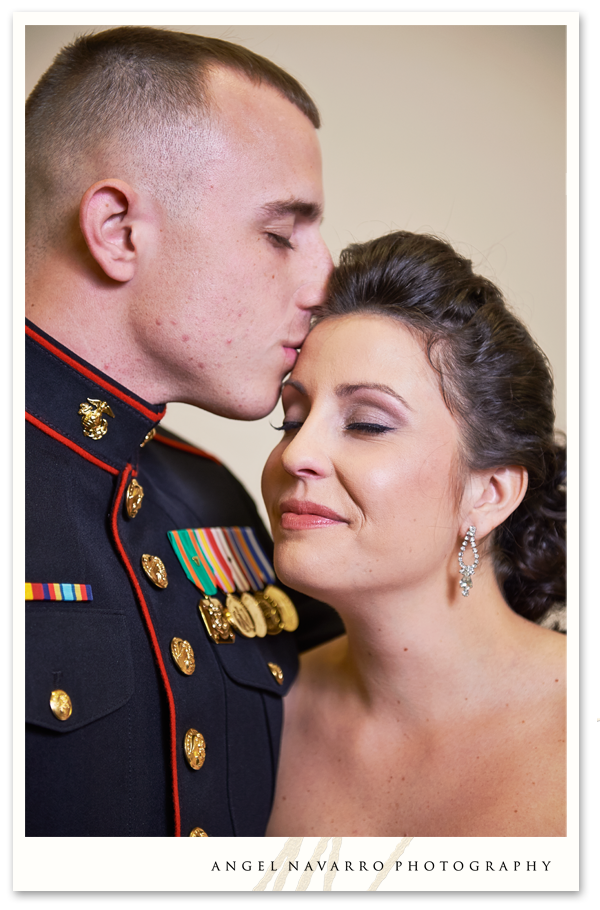 Military brother kisses sister on forehead.