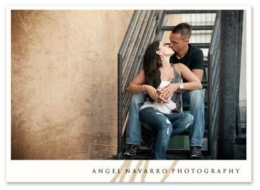 Engaged couple kissing on a stairwell.