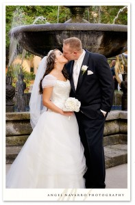 A beautiful wedding portrait of the bride and groom by a fountain.