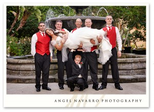 Wedding party holds bride up in the air during wedding picture.
