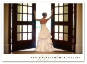 A bride stands at the threshold of a doorway.