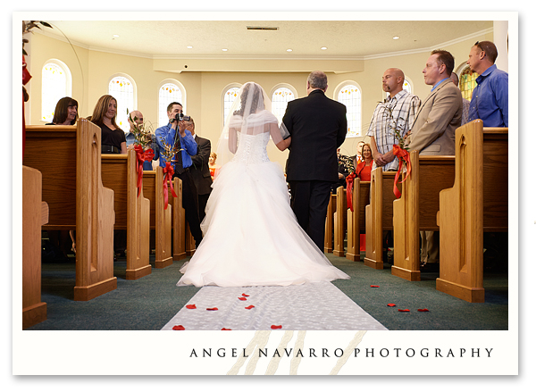 Beautiful photograph of the bride and her father as they walk down the isle towards the groom.