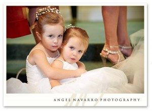 Wedding Photography - Two small bridesmaids sit on the steps of the altar during the ceremony.