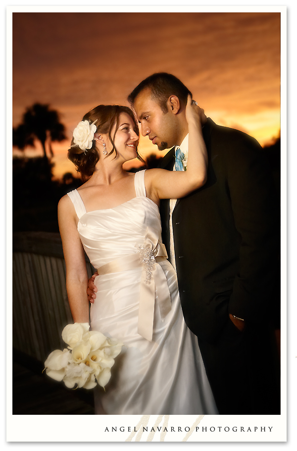 A wedding portrait of the bride and her groom atop a wooden bridge.