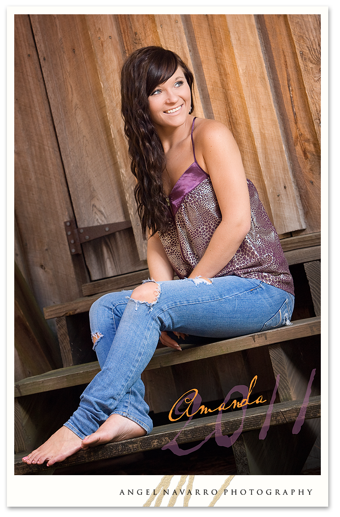 A high senior gal posed in a barn setting setting for her senior picture.