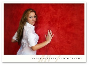 The very pretty Andrea leans up against a red wall for a stunning candid.
