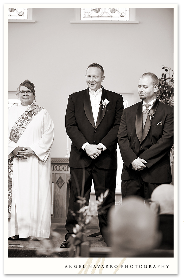 Groom looks upon his bride with joy as she walks towards him on the altar.