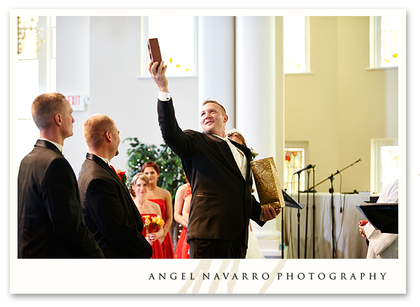 Groom holds up a symbolic gift at their wedding.