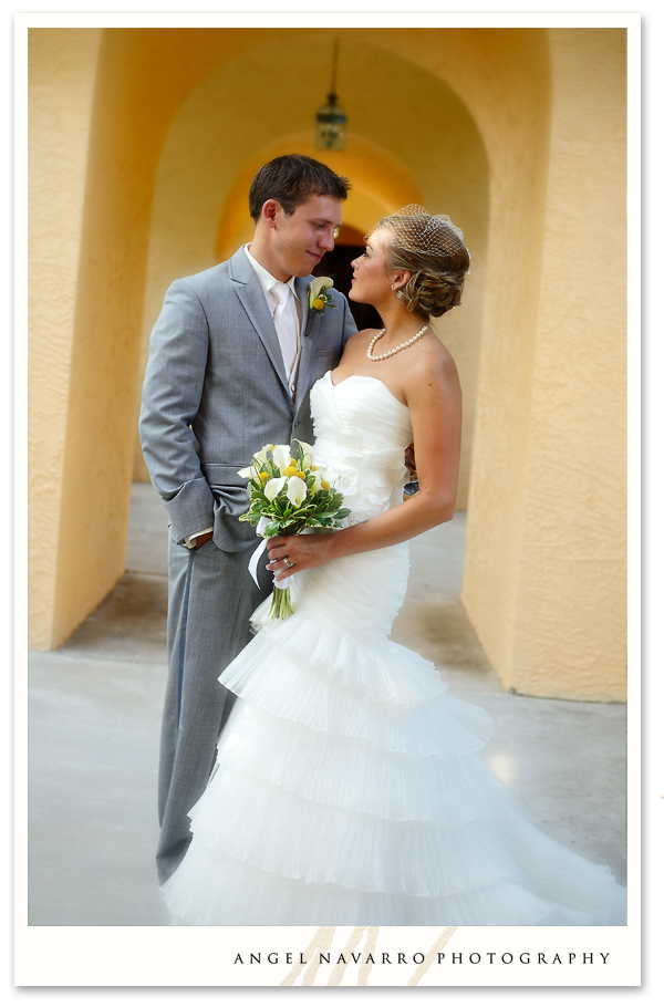 A portrait of the bride and groom in m arched hallway.