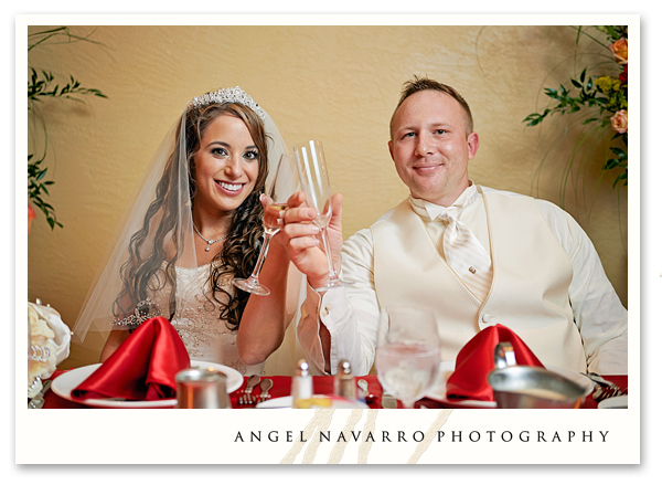 Bride and groom hold toasting glasses for a photograph.
